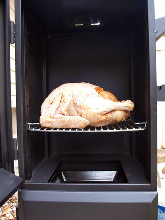 a whole turkey being cooked in a propane smoker grill