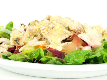 a salad of chicken breast, lettuce, tomato, onion, shredded raw beets, and carrot on a white background