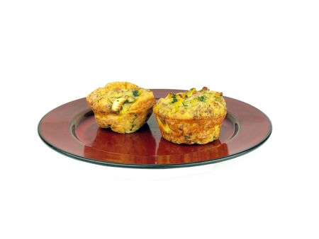 a breakfast of scrambled egg muffins mixed with bacon, onion, spinach, and pepper isolated on white background