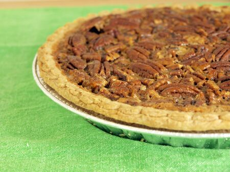 close up image of homemade pecan pie on a green table cloth