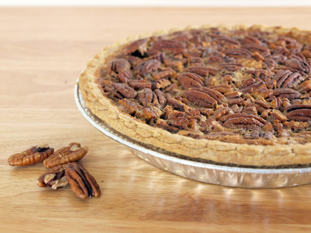 close up image of homemade pecan pie on a  wood table