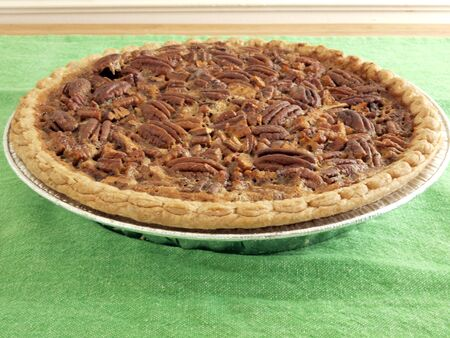 pecan pie: close up image of homemade pecan pie on a green table cloth