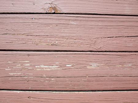 close up photo of  weather beaten painted old wood beams of a deck