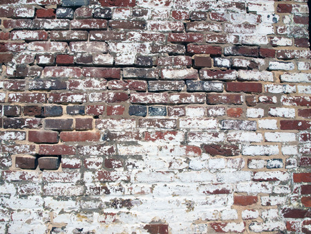 weather beaten: photo of an antique brickwall showcasing its weathered and appearance and texture Archivio Fotografico