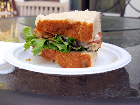a chicken sandwich made with Marco Polo bread, lettuce, tomato, onion, coleslaw and cheese Stock fotó
