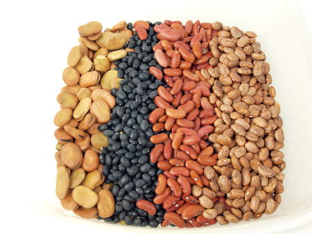 kidney beans: a assortment of dried fava beans, kidney beans, black beans and pinto beans in a container