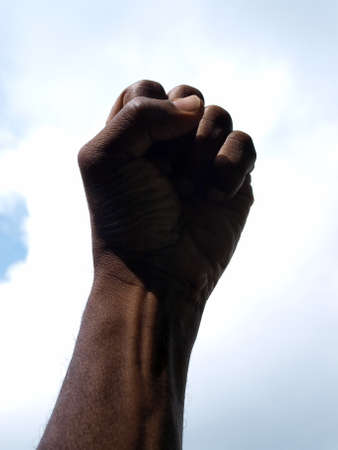 photograph of a African American's clenched hand into a fist to symbolise power and black pride with the sky as a backdrop. Stock fotó - 150710944