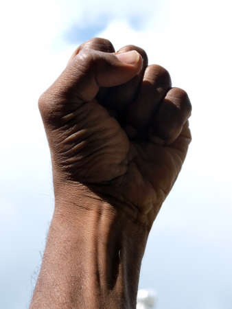 photograph of a African American's clenched hand into a fist to symbolise power and black pride with the sky as a backdrop.