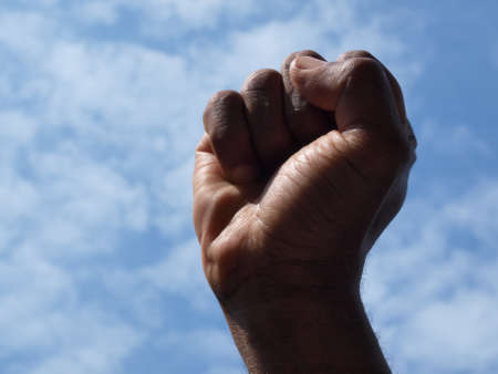 photograph of a African American's clenched hand into a fist to symbolise power and black pride with the sky as a backdrop. Stock fotó - 150710945