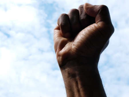 photograph of a African American's clenched hand into a fist to symbolise power and black pride with the sky as a backdrop. Stock fotó - 150580472