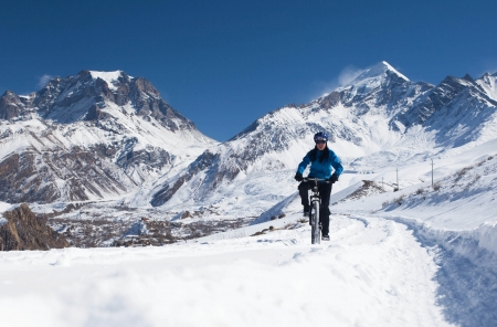 mountain bicycling: girl on bike rides in the snow in the high mountains of the Himalayas  Annapurna track Himalayas