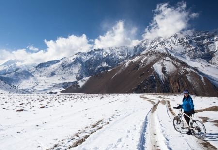 girl on bike rides in the snow in the high mountains of the Himalayas photo