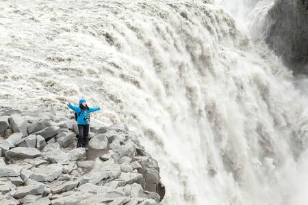 happy girl standing on a cliff waterfall in Iceland photo