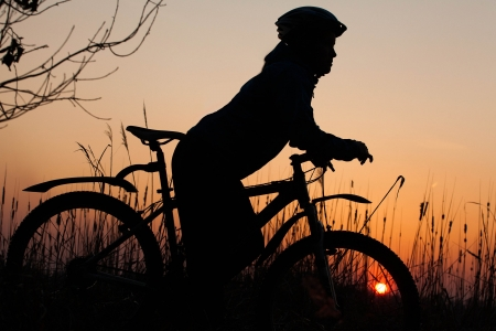 girl silhouette at sunrise with a bicycle photo