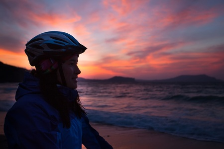 Girl with a bicycle stands on the beach and looks into the distance photo