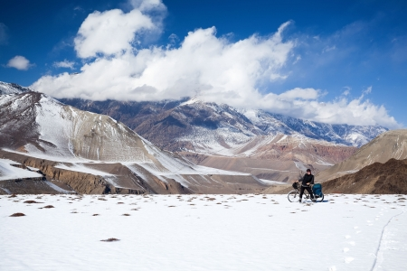 Man on bike rides in the snow in the high mountains of the Himalayas. Annapurna track Himalayas