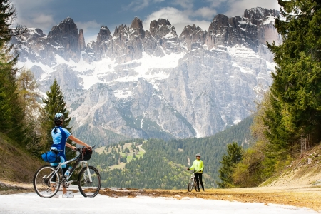 mountain bicycling: Girls with bikes are on the road in the woods and mountains of the Dolomites. Italy.