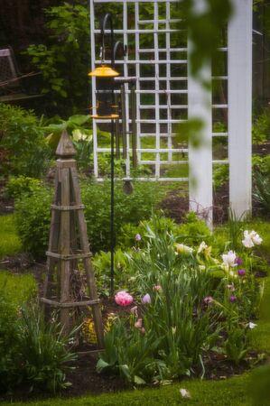 obelisk: Garden on a green lawn, with hummingbird feeder, obelisk, and plants.