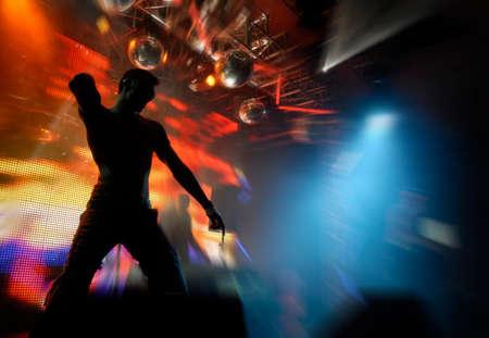 clubbers: claro silueta de bailarina de discoteca en naranja brillante de fondo. buen uso de tarjetas de partido y carteles  Foto de archivo
