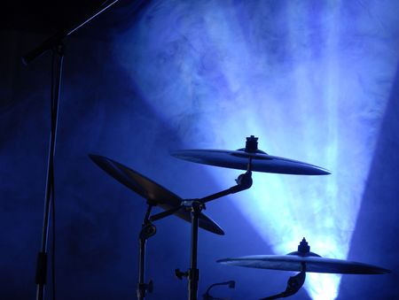 cymbals set in blue light of searchlights. more light