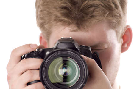 young photographer with digital camera isolated on white (focus on camera, man out of focus). Stock Photo