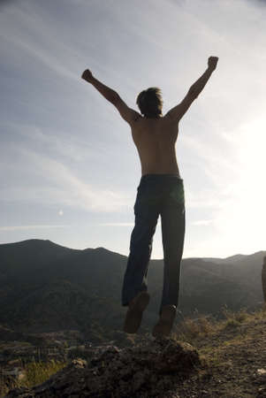conquering: silhouette of freedom person on peak of mountain