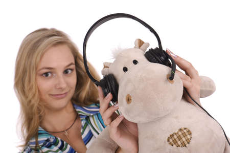 young blonde woman with earphones and soft toy hippopotamus photo