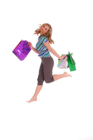 Young pretty woman jumping with bags in her arms photo