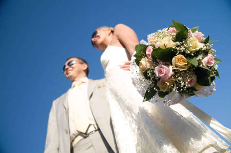 wedding day of young pair. isolated on blue sky. focuse on bouquet photo