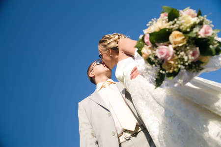 kissing wedding pair isolated on blue sky photo