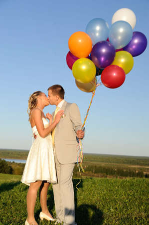 kissing wedding pair in the field photo