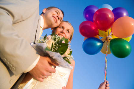 happy young wedding pair with multi-colors balloon isolated on blue sky