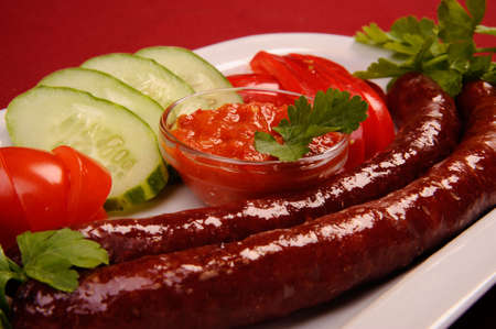 two sausages and vegetables on the white plate photo