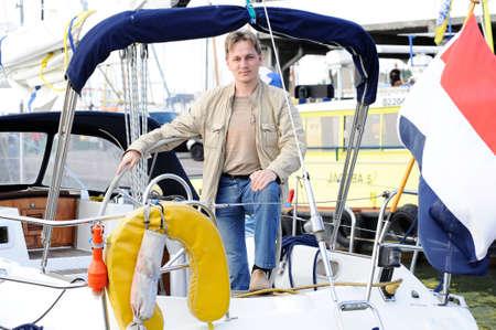 yong man posing near handwheel of yacht photo