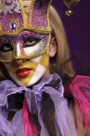 pretty young lady in violet half mask, may be use for joker concept photo