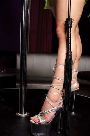 leather flogger and leg of strip dancer in night club photo