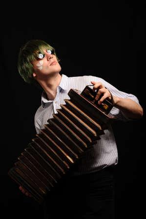 harmonist: young handsome harmonist isolated on black