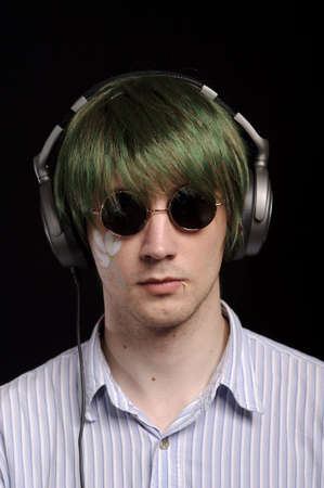 young man with green fake hairs listen to music, isolated on black photo