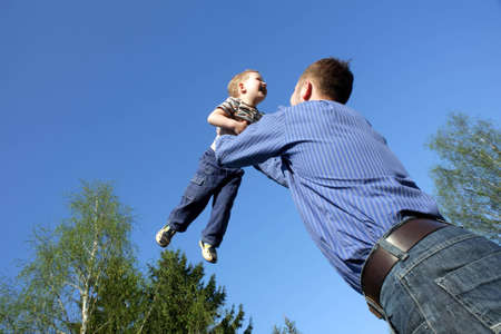 toss: father toss up a child isolated on blue sky