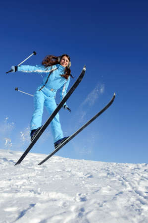 jumping pretty young woman in ski suit full of energy Stock Photo