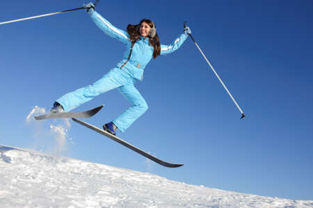 carefree young woman in ski suit jumping, may be use for winter sports cards and posters Foto de archivo