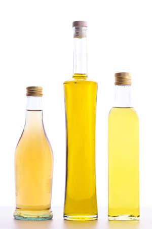 オリーブ オイルと白で隔離されるワイン酢のボトルの閉じたボトル