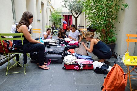 PARIS - AUGUST 08, 2015: girls collect luggage in the hostel. Hostels provide budget-oriented, sociable accommodation where guests can rent a bed in a dormitory and share a bathroom, lounge, and sometimes a kitchen.