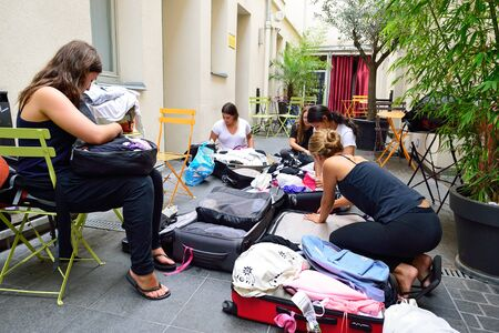 PARIS - AUGUST 08, 2015: girls collect luggage in the hostel. Hostels provide budget-oriented, sociable accommodation where guests can rent a bed in a dormitory and share a bathroom, lounge, and sometimes a kitchen. 新聞圖片