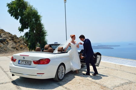 SANTORINI, GREECE - AUGUST 05, 2015: Beautiful young couple bride and groom posing in white cabriolet BMW. Santorini wedding has become very popular throughout the past years. Editorial