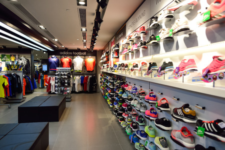 HONG KONG - 02 de noviembre, 2015: una tienda de Adidas en New Town Plaza. Adidas AG es una corporación multinacional alemana que diseña y fabrica calzado deportivo, ropa y accesorios Editorial