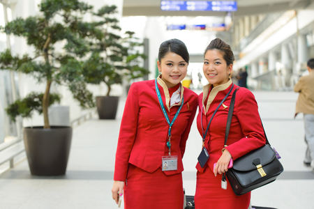 HONG KONG - APRIL 15, 2015: Cathay Pacific crew members posing in airport. Cathay Pacific is the flag carrier of Hong Kong, with its head office and main hub located at Hong Kong International Airport.