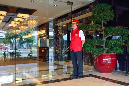 HONG KONG - JUNE 02, 2015: Mandarin Oriental Hotel doorkeeper. Mandarin Oriental Hotel Group, a member of the Jardine Matheson Group, is an international hotel investment and management group with luxury hotels