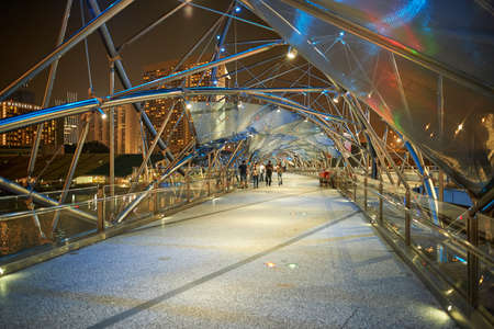 SINGAPORE - NOVEMBER 08, 2015: The Helix Bridge at night. The Helix Bridge is a pedestrian bridge linking Marina Centre with Marina South in the Marina Bay area in Singapore