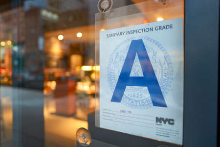 NEW YORK - CIRCA MARCH 2016: close up shot of sanitary inspection grade on the window of Starbucks Cafe. Starbucks Corporation is an American global coffee company and coffeehouse chain based in Seattle, Washington